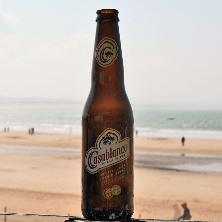 a bottle of Casablanca beer with the beach and coast in the background