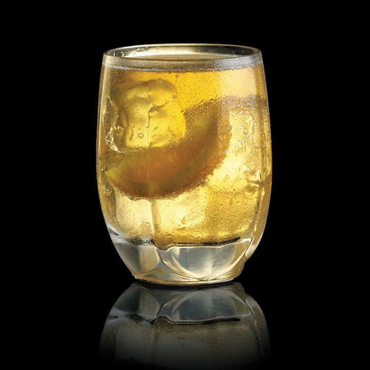 A rounded highball glass holds a vivid yellow drink, a few ice cubes, and a wedge of orange. The glass glows with light on a black background, and is reflected on the dark black base it sits on.