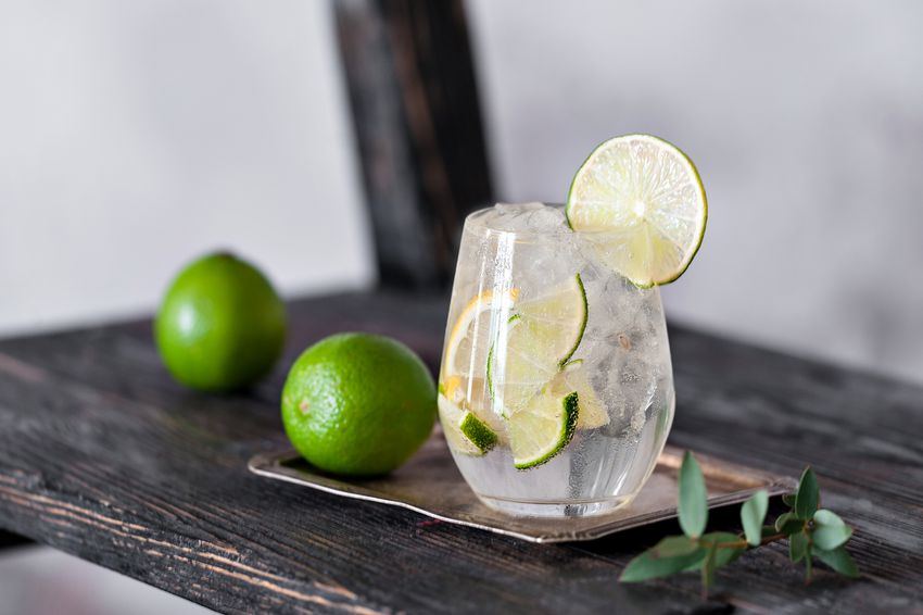 a drink made with vodka and limes on a wooden table