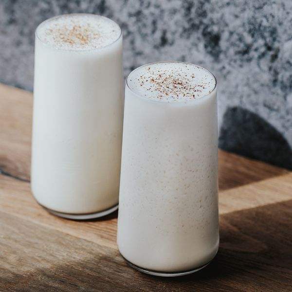 Two tall glasses sit on a wooden surface, a blue and white speckled wall behind them. The glasses are filled to the brim with a creamy white drink and are dusted with nutmeg.