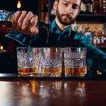 A bearded bartender in a blue plaid shirt pours a stream of Irish whiskey into a patterned rocks glass. Two other glasses flank the center one that he is pouring into, each with a large dram of whiskey.