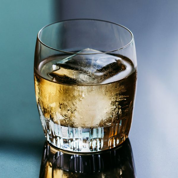 rusty nail cocktail served in a rocks glass over one large ice cube
