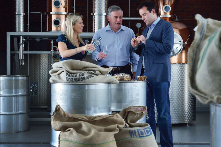 One woman and two men tasting gin inside a distillery