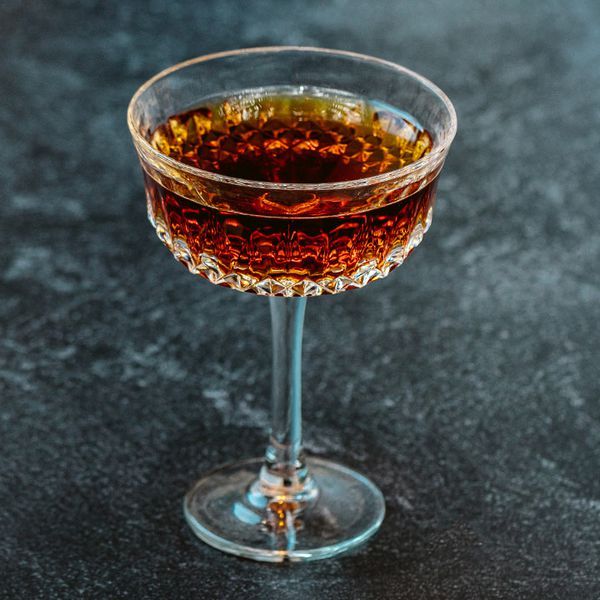 A deep red-brown stirred cocktail in an ornate stemmed cocktail glass against a dark gray background