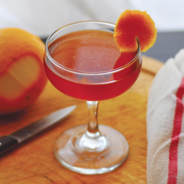 toronto cocktail on a cutting board with an orange and knife