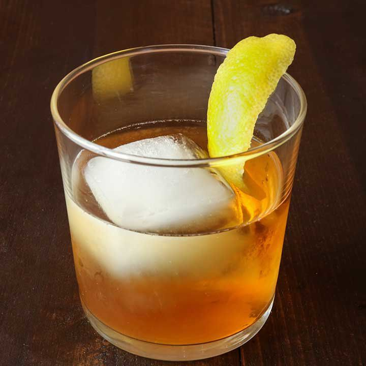 spiced tequila old fashioned in a rocks glass with one large ice cube and a lemon peel garnish