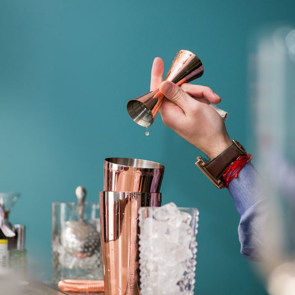 Rose gold jigger pouring into shaker tins