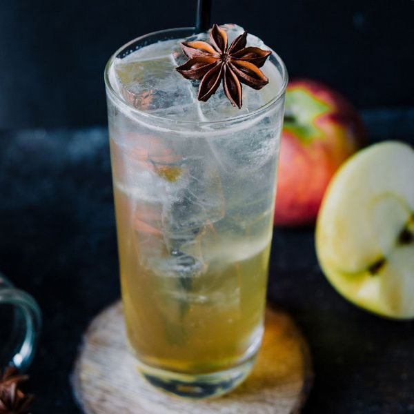 A highball glass rests on a wooden coaster against a dark blue surface. The glass is filled with ice and a light brown highball, and is topped with a star anise. A few apples are strewn on the blue surface, out of focus.