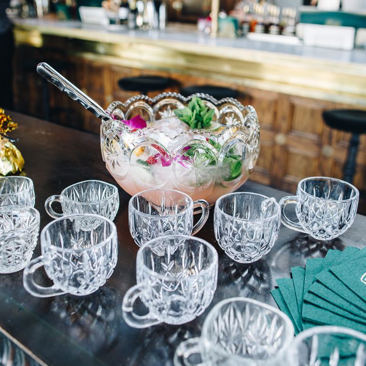A large, elaborate punch bowl sits on a black counter top surrounded by empty glass mugs. The punch within is light pink and garnished with mint and flowers.