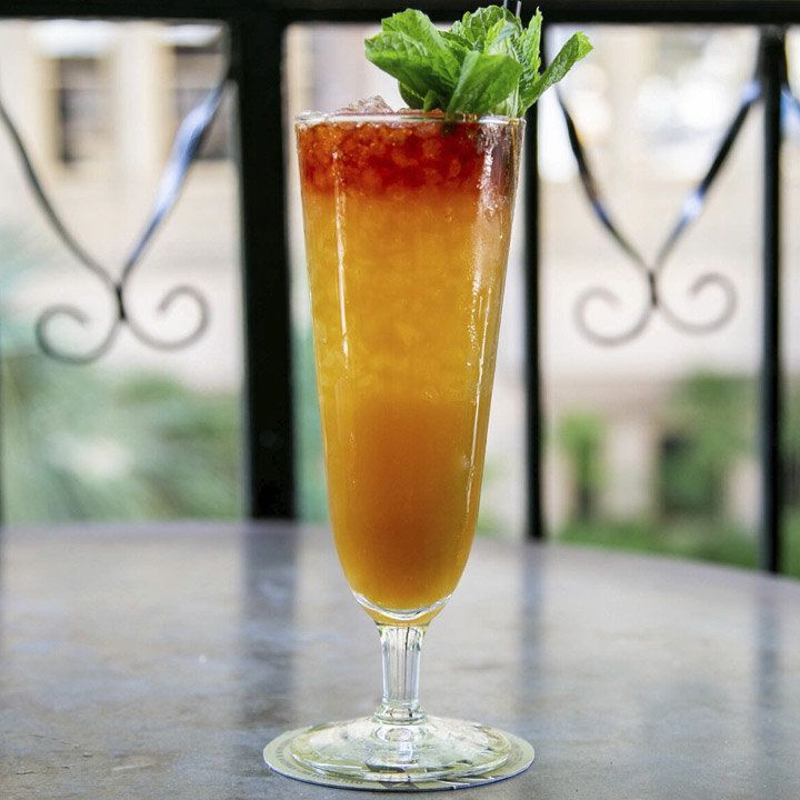 A tall glass holds a multi-layered drink, going from deep red at the top to orange mixed with crushed ice and then a thick and opaque orange base. The drink is garnished with a generous sprig of mint, and served on a table on a balcony.