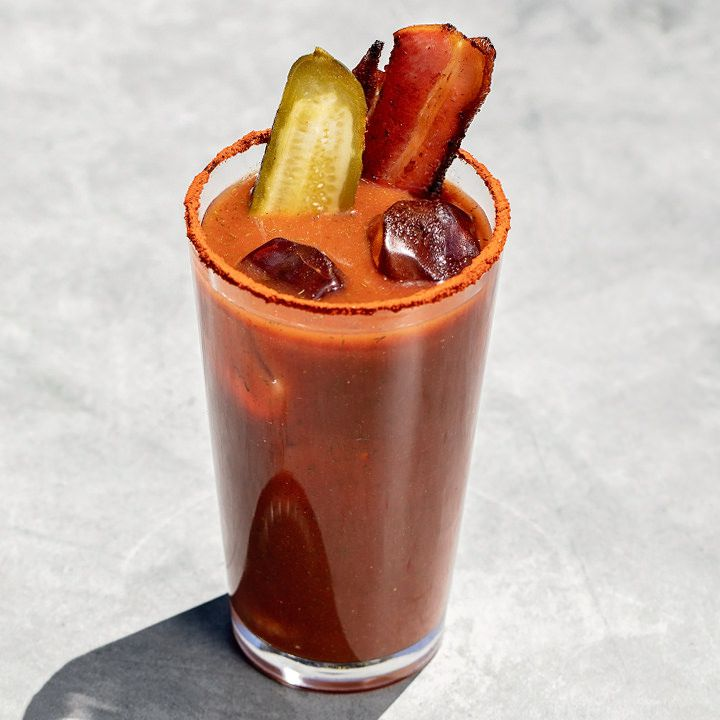 A Bloody Mary in a tall, narrow pint glass rests on marble. The drink is garnished with a pickle skewer and bacon slice, and the glass is rimmed with dusty red spices.