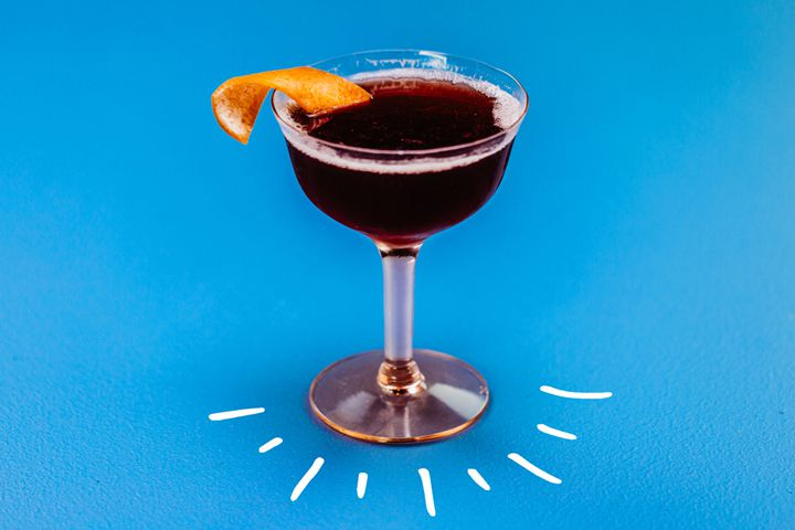 Photo illustration of deep red Improved Dunlop cocktail in coupe glass on blue background with white hand-drawn lines
