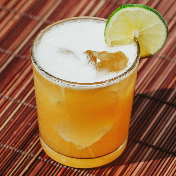 Jamaican Breeze cocktail in a rocks glass over ice with a lime wheel garnish, served on a red straw mat