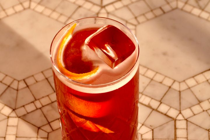 An effervescent cherry-red drink in a highball glass with a long citrus twist and a geometric tile background