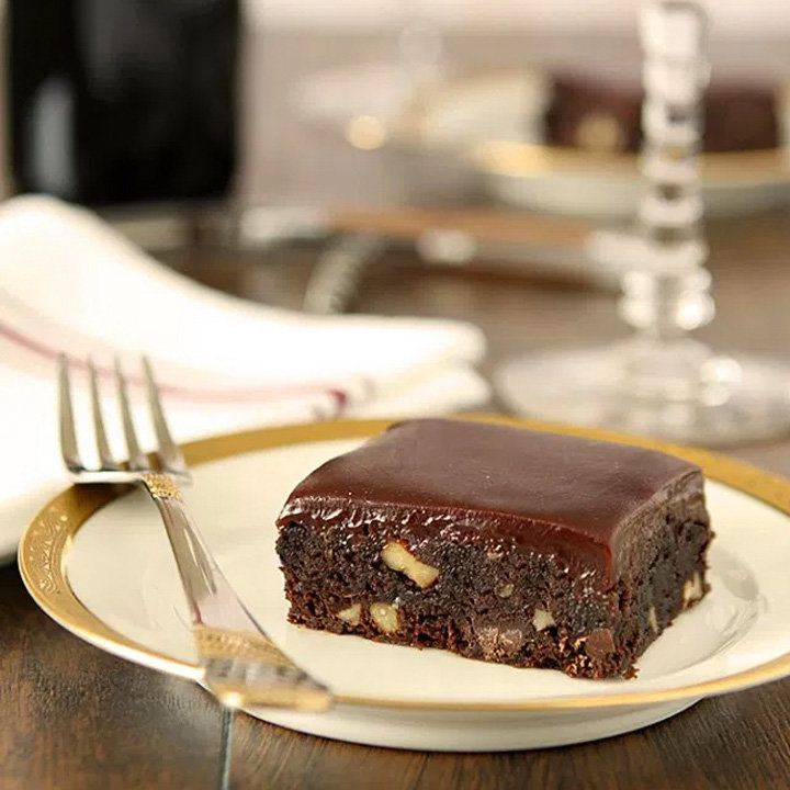 A brownie rests on a white plate with a gold rim. The brownie is filled with nuts and topped with a shiny glaze. An elegant fork rests next to it on the plate, and a napkin is hazy in the background.