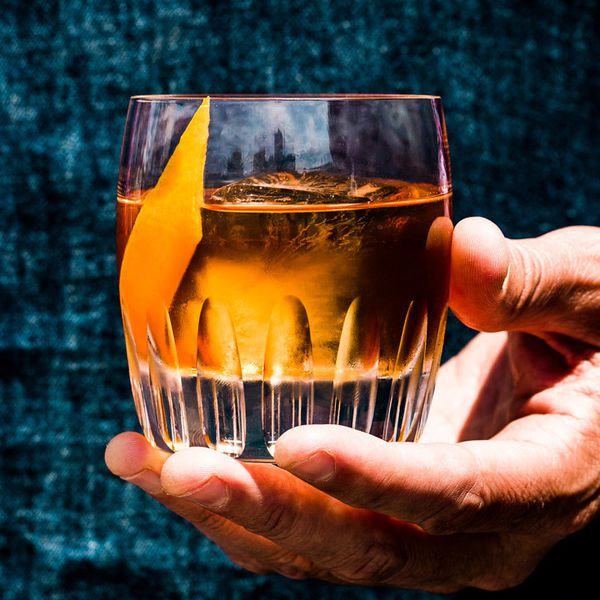 hand holding the Benton's Old Fashioned cocktail in a rocks glass with an orange peel garnish
