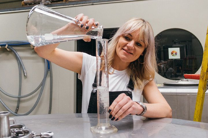 Morgan McLachlan pours liquid from a beaker into tube