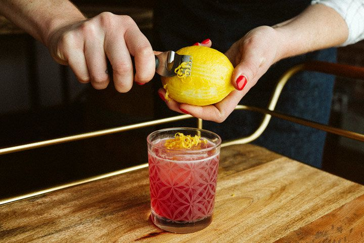 A woman's hands peel long, thin strips of zest from a lemon, piling them on top of an ice cube floating in a vividly red drink.