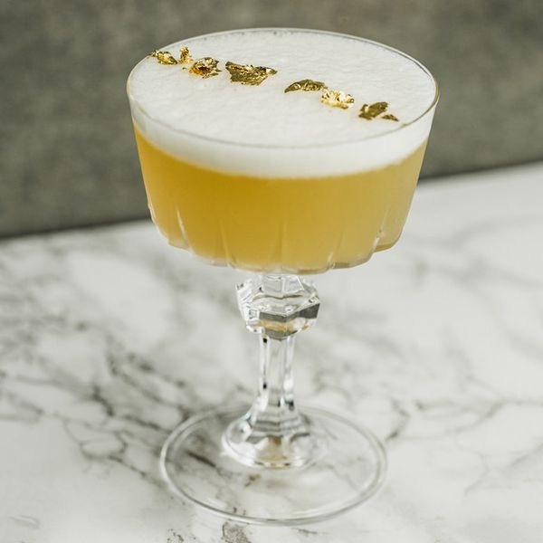 An elegant, chunky coupe rests on a marble counter with a gray wall behind it. The glass is filled with a golden drink with a thick foam head. Six flakes of edible gold rest on the foam in a line.