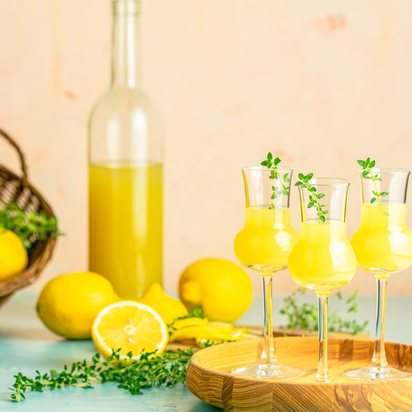 Limoncello with thyme in grappas wineglass with water drops on light concrete table.