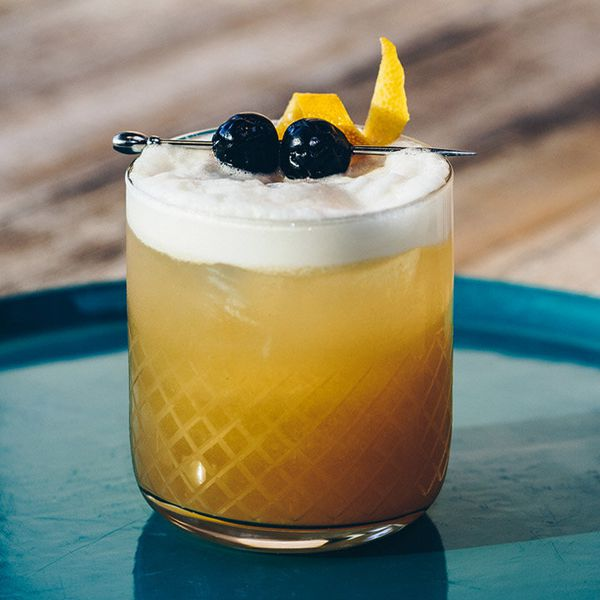 amaretto sour cocktail garnished with two cherries and a lemon twist