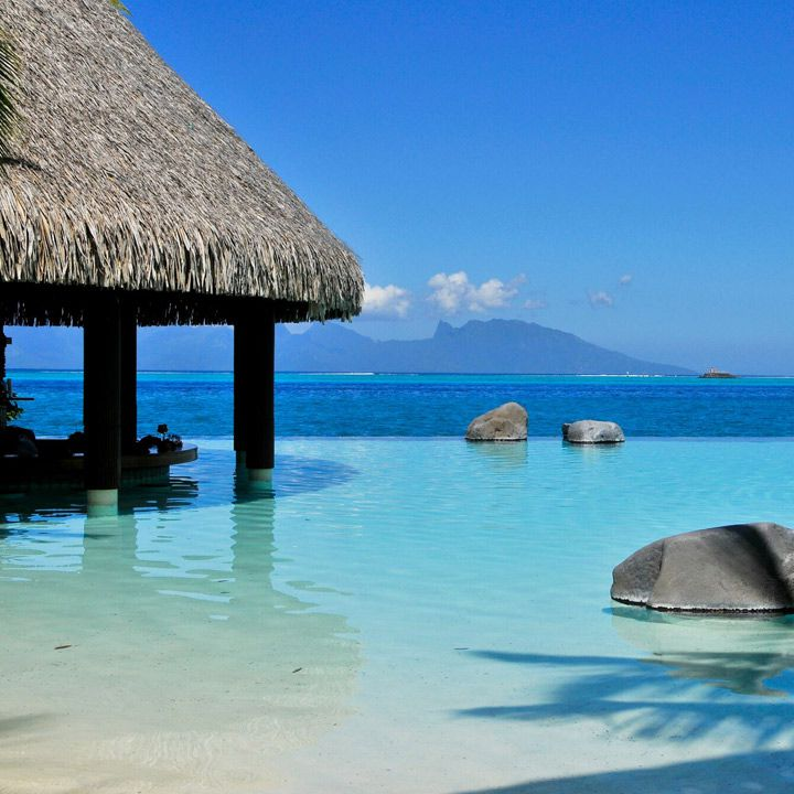 InterContinental Tahiti swim-up bar. Expanses blue water forever and a thatched bar-hut in front