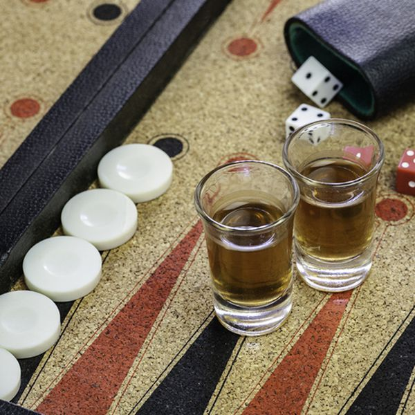 Two full shot glasses on a backgammon board close up.