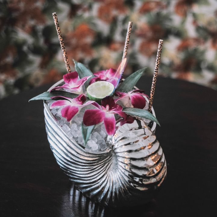 Warm in the Winter cocktail in a silver nautilus shell, garnished with orchids, pineapple fronds and cheetah-print straws