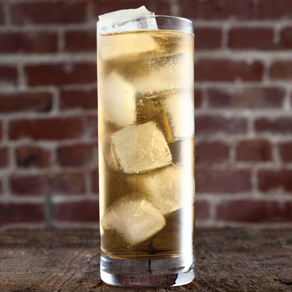 7&7 cocktail in a highball glass with several ice cubes, set against a red brick background