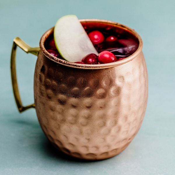 A copper mug with a handle and hammered finish sits on a blank, blue backdrop. The mug is filled with ice, and garnished with fresh ripe cranberries and a slice of green apple.