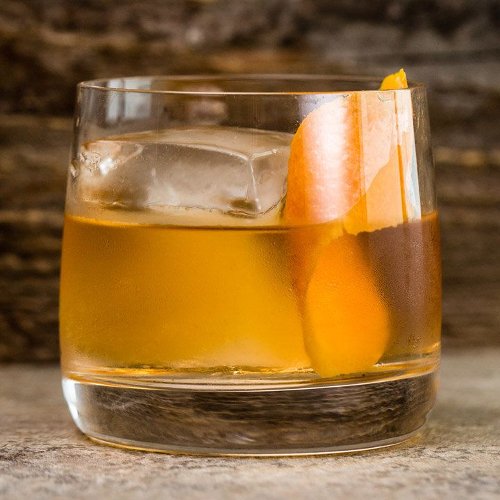 Oaxacan Old Fashioned with one large ice cube and orange peel garnish