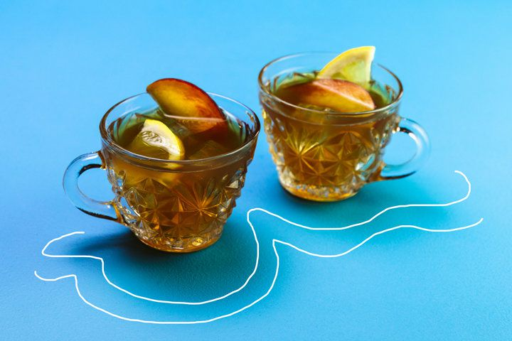 Two tea cocktails in clear tea cups garnished with lemon and peach slices