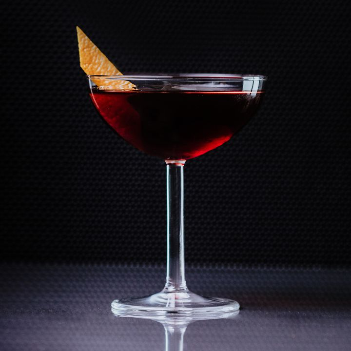A Martinez cocktail in a coupe glass garnished with orange zest