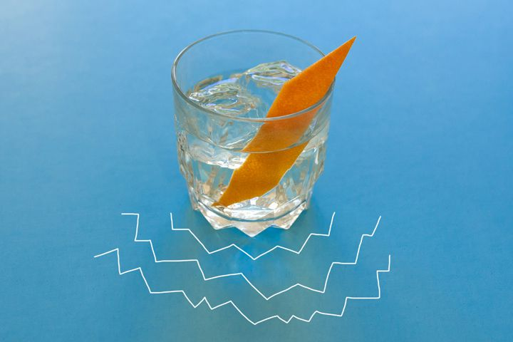 The clear Quill Riff cocktail, served on a large chunk of ice and garnished with a manicured orange twist