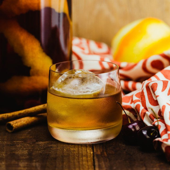 A short, wide rocks glass with thin walls rests on a dark wood surface. It's filled with dark whiskey and a large ice cube, and surrounded by a red and white cloth, cinnamon sticks, a jar and a partially peeled lemon.