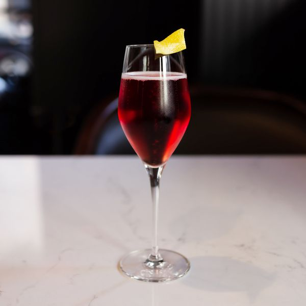 A Champagne flute rests on a marble bar top. It's filled with a red sparkling drink and garnished with a lemon peel.