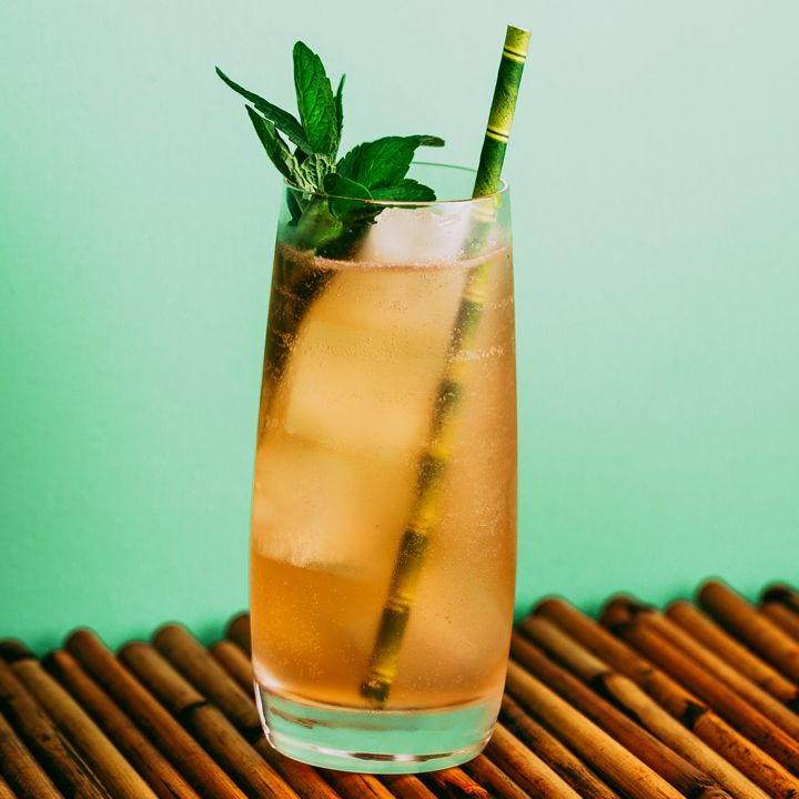 Suffering Bastard cocktail with bamboo straw and mint garnish