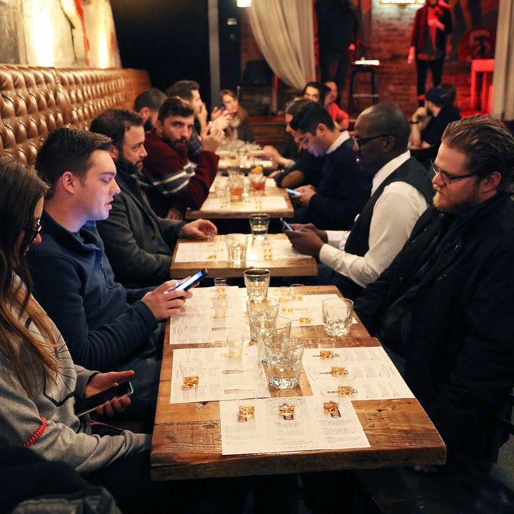 Tour participants sitting at several tables in a bar with whiskey glasses before them.