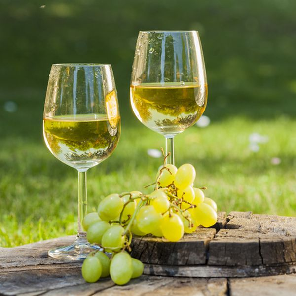 white wine with white grapes on a wooden table
