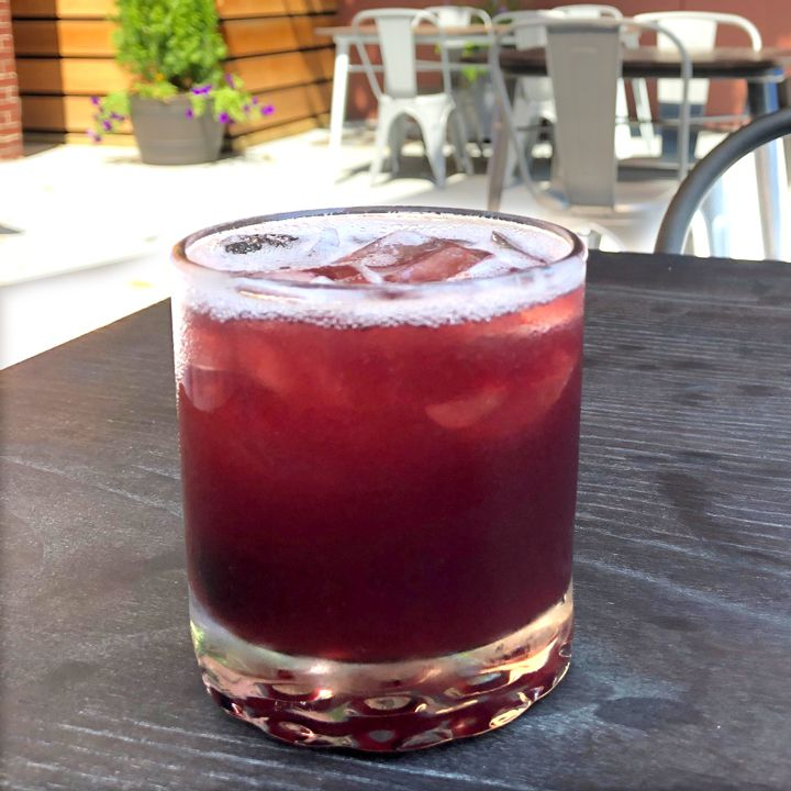 A rocks glass sits on a wooden table on a sunny patio. It's filled with a vivid red cocktail over ice.