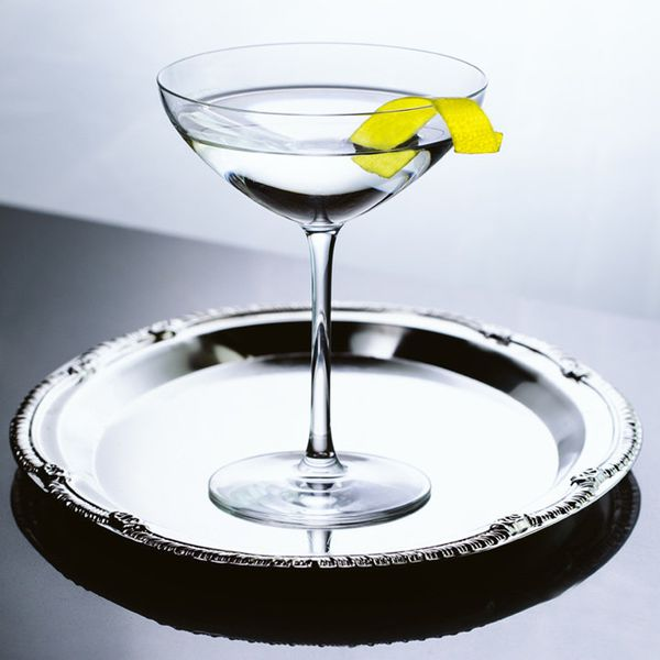 A swooping martini glass sits on a silver platter. Only the bright yellow lemon peel draped over the lip of the glass gives the otherwise crystalline and silver image any color