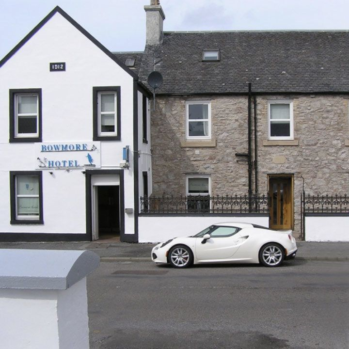 Bowmore Hotel exterior, its main entrance features a roof coming to a V point and a whitewashed exterior