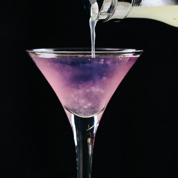 Lemon juice being poured into the Color Changing Martini, turning it from purple to pink