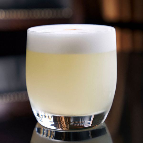 xA light yellow, frothy Pisco Sour in a rocks glass on a black reflective surface