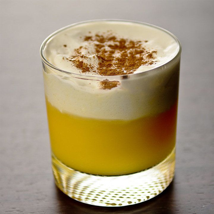 A short, thick-based rocks glass is filled with a Gaelic Flip; golden on the bottom and topped with off-white foam, the drink is generously garnished with nutmeg. The background is a dull gray.