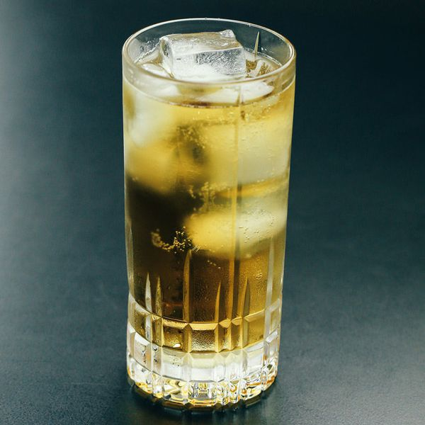 ginger ale highball cocktail with ice, served against a dark backdrop
