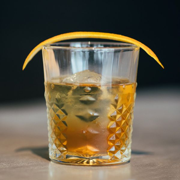 Forefathers cocktail in a textured rocks glass with one large ice cube and a large orange peel balanced on the rim
