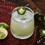 spicy margarita cocktail on a red placemat with limes and jalapeños