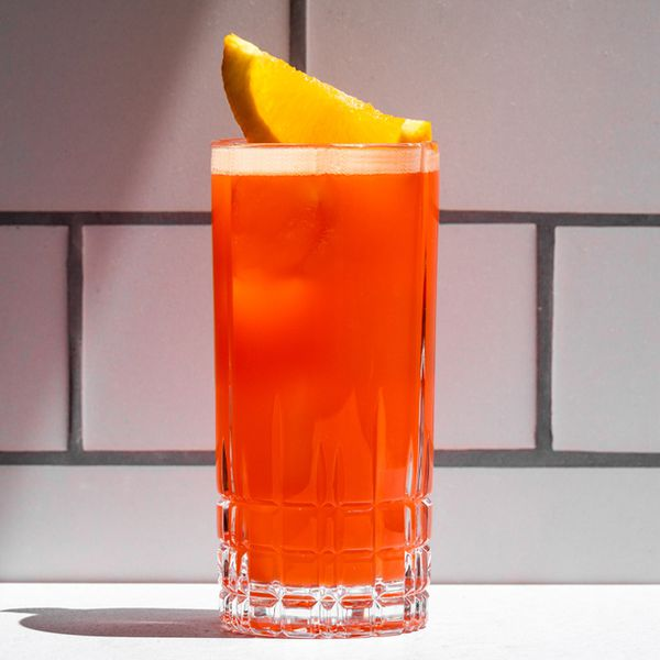 An etched Collins glass containing a frothy orange-red cocktail, garnished with an orange wedge and set against a white subway-tiled background