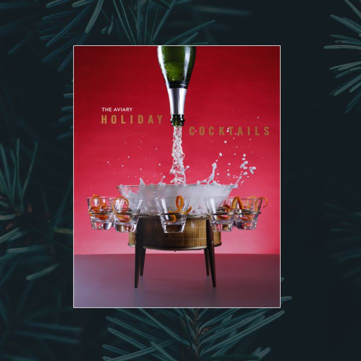 The Aviary: Holiday Cocktails cover featuring a red-to-white gradient background and a bottle of sparkling wine being poured from the top of the cover into a barrel-esque punch bowl with five orange zest-garnished glasses attached
